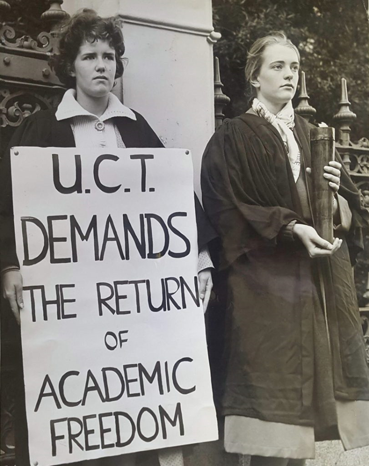 """A woman holds a placard saying """"UCT demands the return of academic freedom"""" beside a woman holding a lit torch. They are both wearing academic dress."""