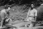 Two men are seated at an archaeological site.